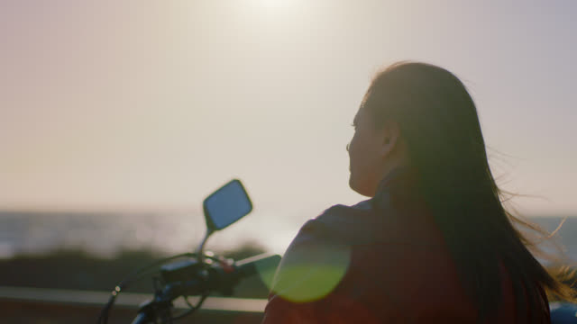 ms slo mo. woman on motorcycle takes helmet off and shakes hair on windy day beside the ocean. - motorrad stock-videos und b-roll-filmmaterial