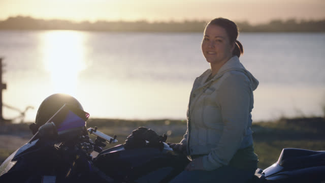 Woman on motorcycle turns and smiles at camera by riverside.