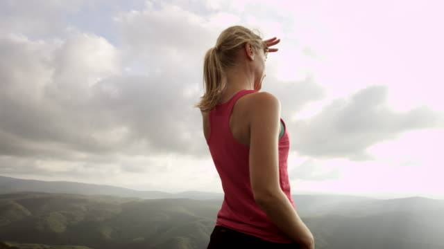 pan woman on mountain top looking into the distance - top garment stock videos & royalty-free footage