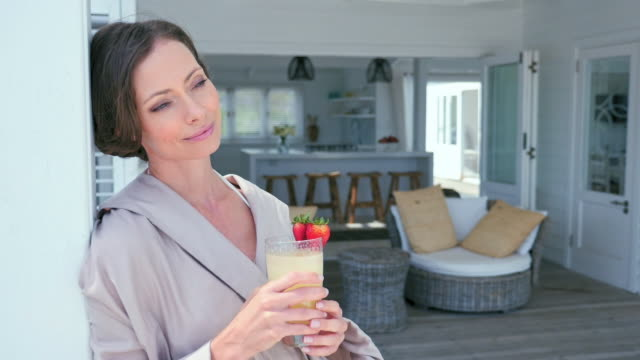 woman on patio - bademantel stock-videos und b-roll-filmmaterial