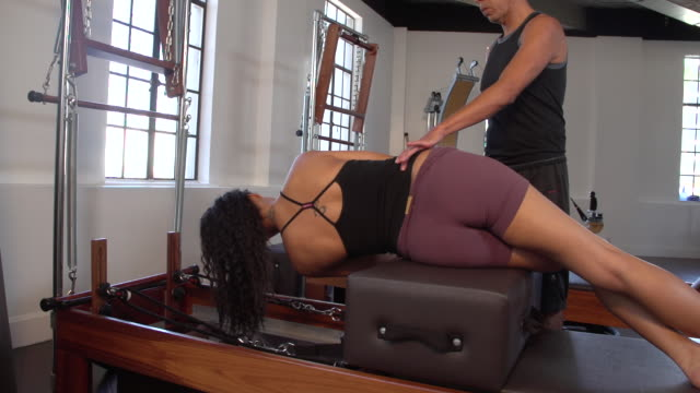 "vidéos et rushes de ""ms pan woman on pilates reformer doing side bends with instructor / beverly hills, california, united states"" - s'étirer"