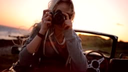 Woman on road trip sitting in convertible and taking photos
