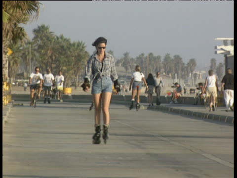 stockvideo's en b-roll-footage met woman on roller blades wearing denim shorts and sunglasses skates towards camera along promenade. palm trees cyclists and other skaters in background venice beach - venice california