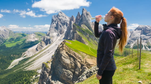 woman on seceda mountain exploring dolomites, hydrating from a reusable water bottle - cold drink stock videos and b-roll footage