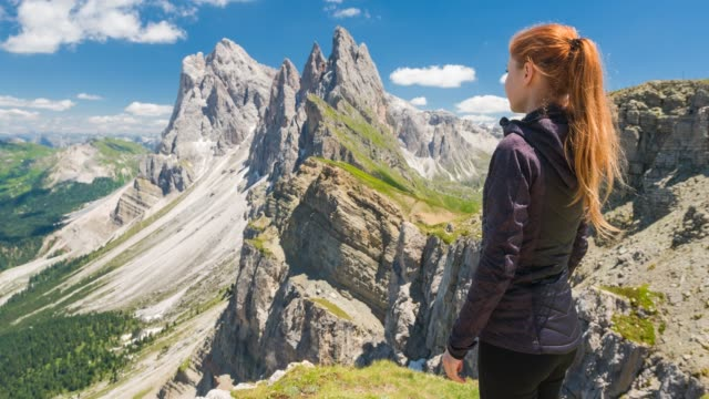 woman on seceda mountain in dolomites, italy looking at breathtaking view - paesaggio spettacolare video stock e b–roll