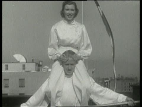 1936 B/W woman on shoulders of man walking on tightrope / Los Angeles / NO AUDIO
