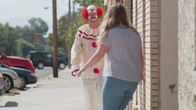 Woman on sidewalk running away from harmless clown / American Fork, Utah, United States