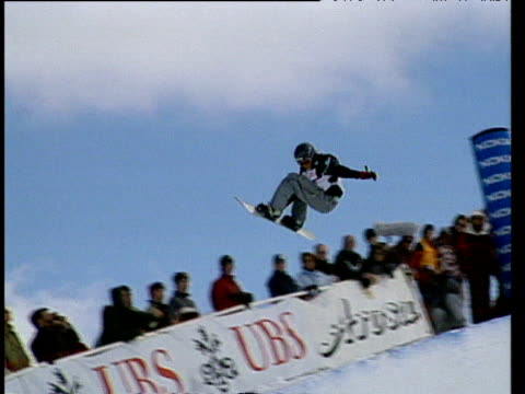woman on snowboard rides half pipe ramp and performs grab tricks during competition switzerland - kopfbedeckung stock-videos und b-roll-filmmaterial