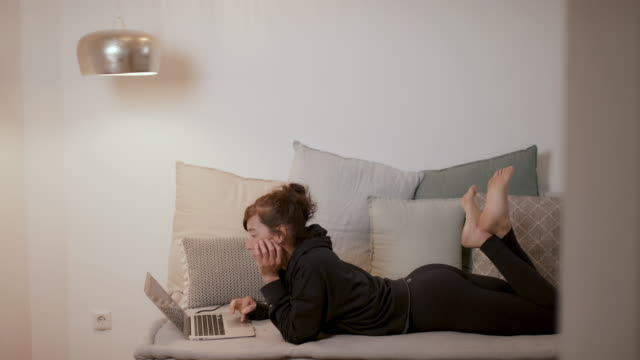 woman on sofa looking at laptop working at home - lying down stock videos & royalty-free footage