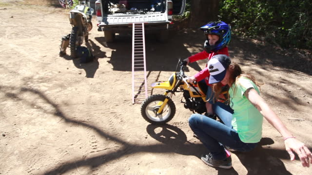 a woman on squatting down calling over a young boy while another young boy is behind her on a dirt bike - kelly mason videos stock videos & royalty-free footage