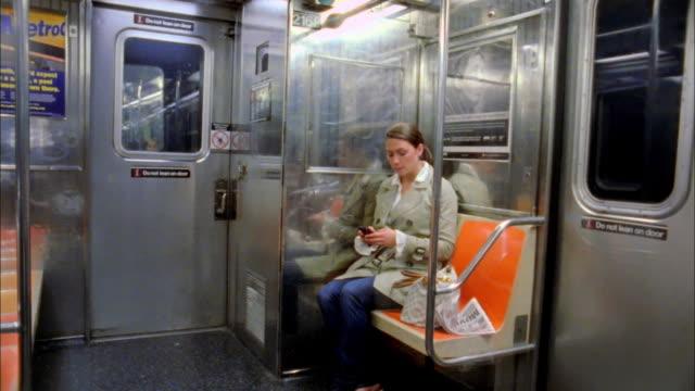 ws woman on subway train text-messaging, new york city, new york, usa - 乗り物内部点の映像素材/bロール