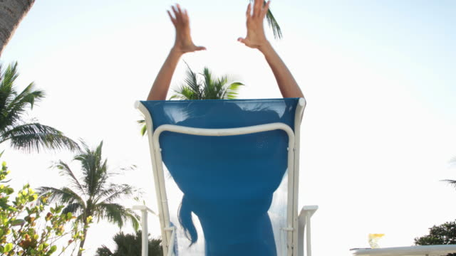 Woman on sun lounger lifts arms out to embrace the sun, silhouetted in sun lounger