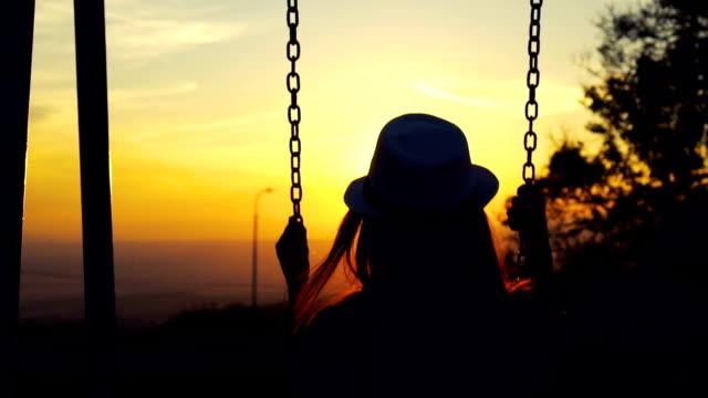 vídeos de stock, filmes e b-roll de mulher em balanço, olhando o pôr do sol - sentando