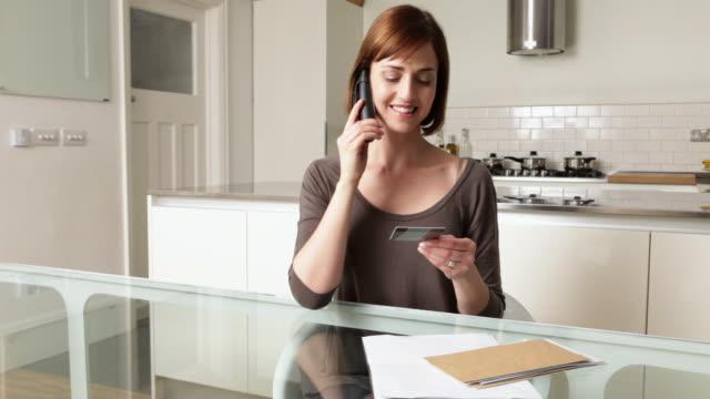 vídeos de stock e filmes b-roll de woman on telephone with credit card - telefone sem fio