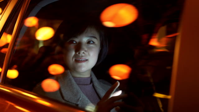 woman on the back seat of a car at night - chinese ethnicity stock videos & royalty-free footage