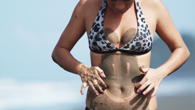 woman on the beach covered with sand drawing a smiley face on her stomach - belly stock videos & royalty-free footage