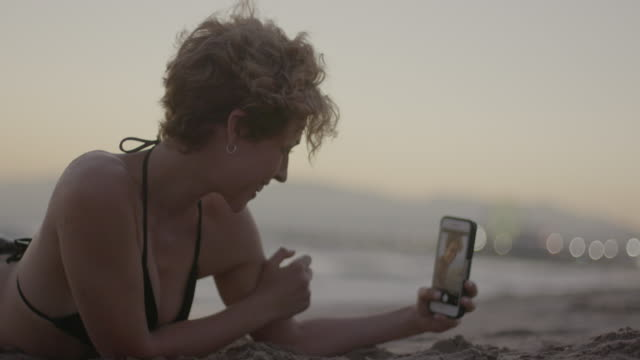 vídeos de stock, filmes e b-roll de woman on the beach with phone - imagem a cores