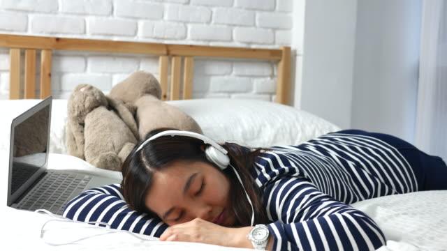vídeos y material grabado en eventos de stock de mujer en la cama escuchando música con el ordenador portátil - auriculares equipo de música