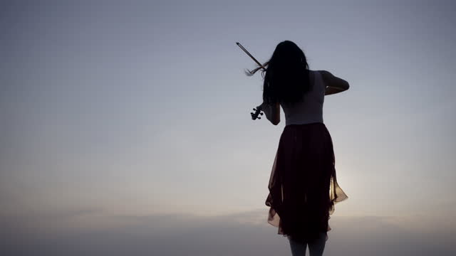 woman on the mountain playing the violin on sea background at sunset . - performing arts event stock videos & royalty-free footage