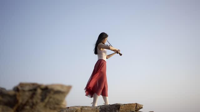 vídeos de stock e filmes b-roll de woman on the mountain playing the violin . - áudio disponível online