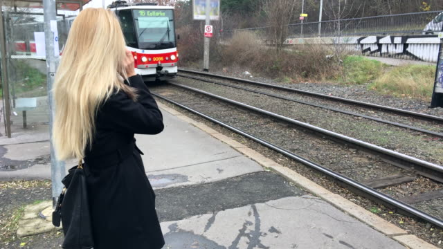 vídeos de stock e filmes b-roll de mulher ao telefone enquanto eléctrico próxima - linha do elétrico