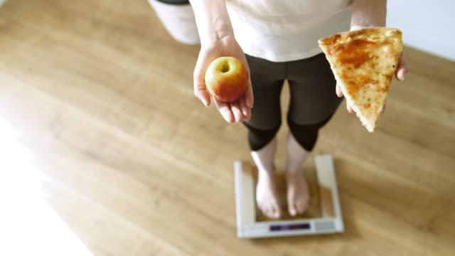 リンゴまたはピザのスライスの間で選択スケールでslo mo女性 - 体重計点の映像素材/bロール