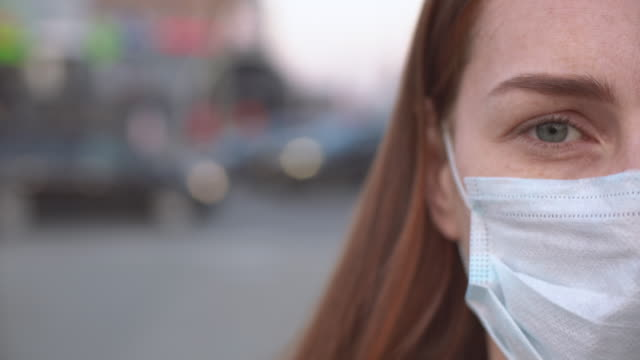 donna per strada con una maschera protettiva - virus dell'influenza aviaria video stock e b–roll