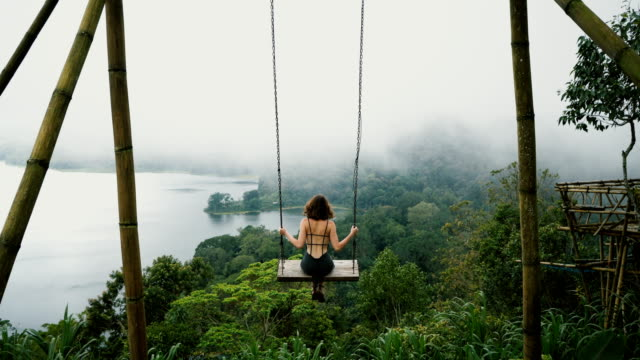vídeos de stock e filmes b-roll de woman on the swing over the jungles and lake  in bali - indonesia