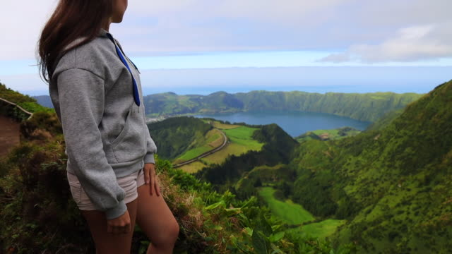 woman on the top of mountain with volcano crater view in the azores. - atlantikinseln stock-videos und b-roll-filmmaterial