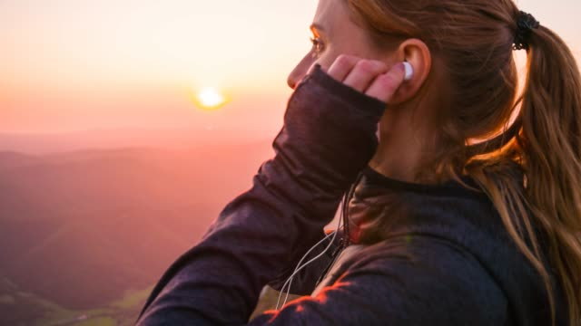 woman on top of mountain looking at sunset, inserting earphones - cuffia attrezzatura per l'informazione video stock e b–roll
