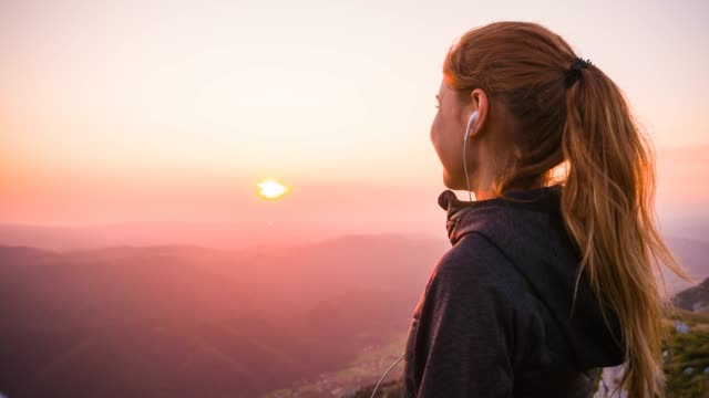 woman on top of the mountain looking at sunrise - cuffia attrezzatura per l'informazione video stock e b–roll