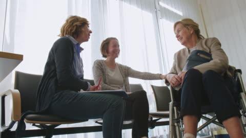 kvinna på rullstol gästande läkare med dotter - besök bildbanksvideor och videomaterial från bakom kulisserna
