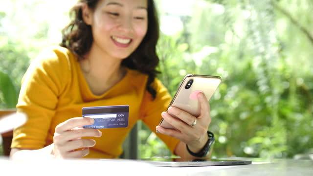 frau online-shopping auf smartphone mit kreditkarte, online-shopping-konzept - portable information device stock-videos und b-roll-filmmaterial