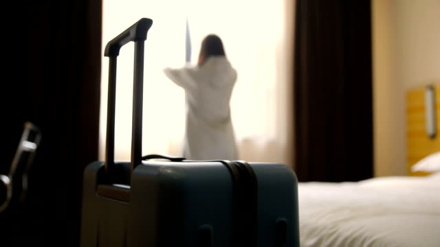woman open curtain in hotel room with luggage - journey stock videos & royalty-free footage