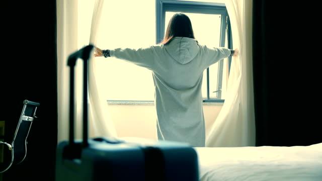 vídeos de stock, filmes e b-roll de mulher abre a cortina no quarto de hotel com a bagagem - olhar para vista