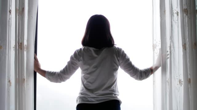 vidéos et rushes de rideau ouvert de la femme dans la chambre à coucher - brightly lit