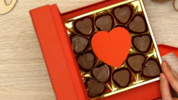 Woman open gift box with heart-shaped chocolate candies aphrodisiac, top view