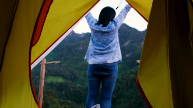 woman open tent and walk out to breathe fresh air at mountain view in sunset time on vacation time - tenda video stock e b–roll