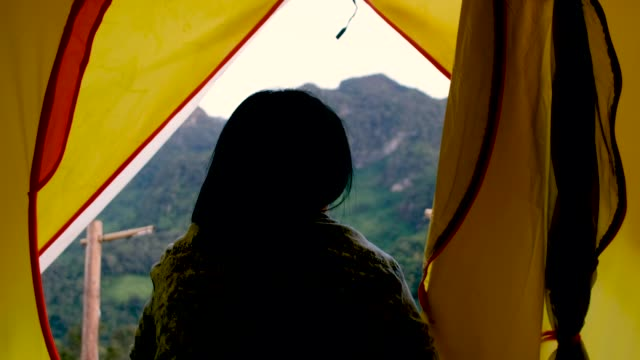 woman open tent and walk out to breathe fresh air at mountain view in sunset time on vacation time - campeggiare video stock e b–roll