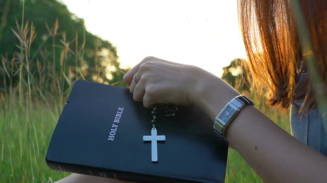 Woman open the bible and cross hanging over