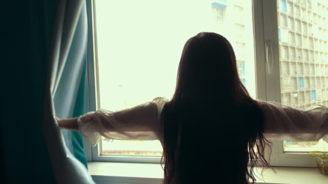 woman open the curtain in morning