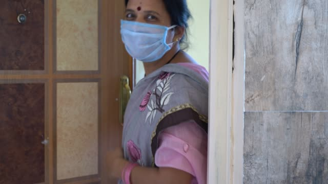 vídeos de stock, filmes e b-roll de woman open the door with face mask during coronavirus pandemic. - idoso na internet