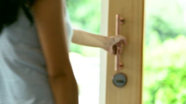 woman open the glass door and going outside. - ingresso video stock e b–roll
