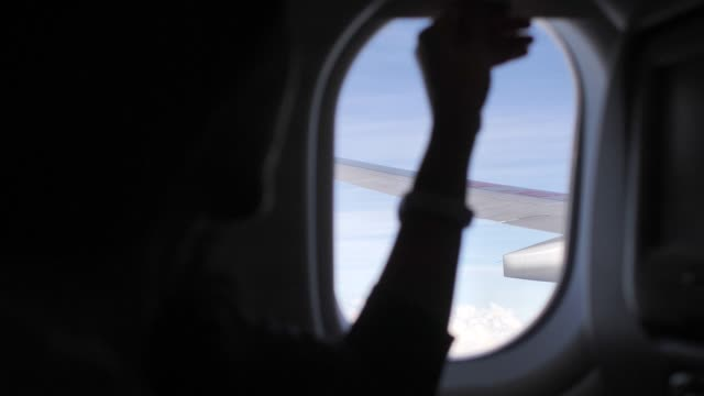 woman open the window on airplane - motore d'aeroplano video stock e b–roll