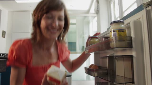ms woman opening and then closing fridge / london, uk - open refrigerator stock videos & royalty-free footage
