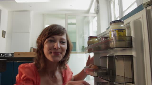 vídeos y material grabado en eventos de stock de ms woman opening and then closing fridge / london, uk - frigorífico