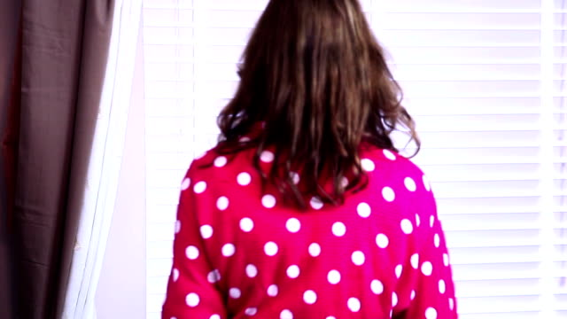 woman opening blinds, looking through window. morning. - blinds stock videos & royalty-free footage