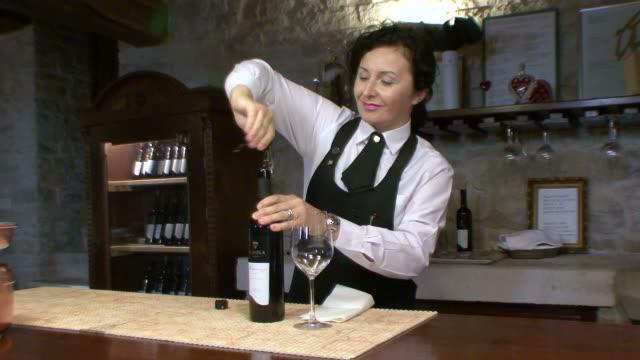 ms woman opening bottle of wine and preparing to pour it / kremenje, croatia   - ボトルオープナー点の映像素材/bロール