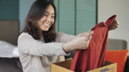 Woman opening Cardboard Box at home