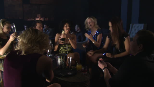 MS Woman opening champagne for friends in bar / London, UK